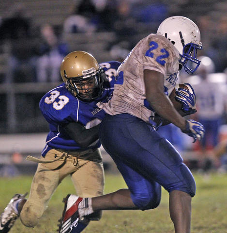 New Kent's Mikel Chalmers, right, runs through the tackle of Smithfield's Darian Bowden, left, during Monday's game at Smithfield.