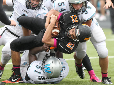 Dalton Durant (54) and Terrell Blocker of Warhill draggs down Bailey Hicks of Tabb after a run during the fourth quarter Saturday at Bailey Field.