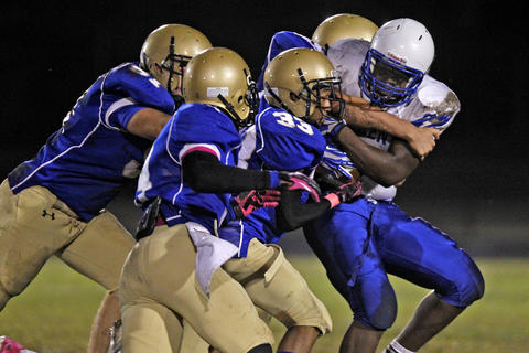 New Kent's Mikel Chalmers, right, drags Smithfield's Darian Bowden, center, 33, and other defenders during Monday's game at Smithfield.