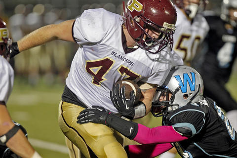 Poquoson's Grayson Boyce runs through the tackle of Warhill's Bryce Koob, right, during Thursday's game at Wanner Stadium.