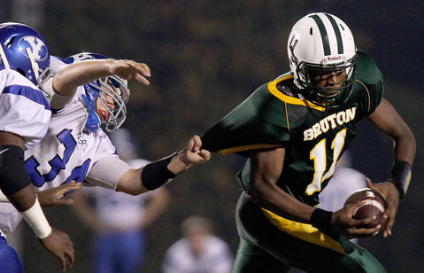 Bruton quarterback Bilal Wallace tries to get away from Alec Mang of York during the first quarter Friday at Bruton.