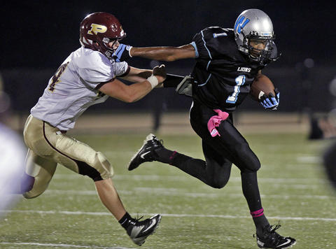 Poquoson's Matthew Titlow, left, chases down Warhill's Reggie Lipscomb during Thursday's game at Wanner Stadium.