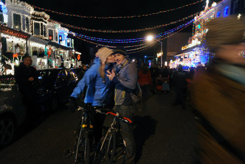 Jessica Curtis, left, kisses her boyfriend Mike Shisler under the lights in Hampden. The two rode their bikes from Canton to Hampden for the annual lighting.
