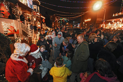 Santa Claus sits with children after counting down to the annual lighting of the display.