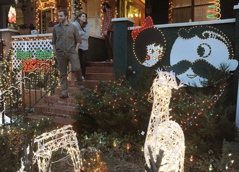 Shown are Steve Saada and Jessica Baroody on the steps of their Natty Boh and the Utz Girl-themed Christmas display at his home on 34th street in Hampden.