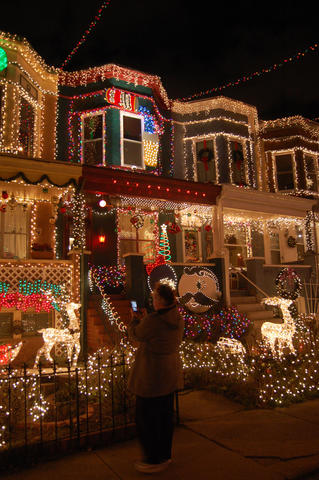 A visitor takes pictures of the decorations on Hampden's 34th Street.
