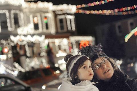 Carolyn Johnson carries her niece, Etta Colantuoni, 20 months, both of Hampden, as they enjoy the holiday light display on 34th Street in Hampden.
