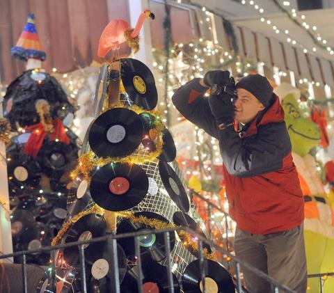 Jeff Kniple of Rodgers Forge, photographs an LP Christmas tree with a pink flamingo on top. This is one of many eye-catching decorations in the holiday light display on the 700 block of 34th Street in Hampden.