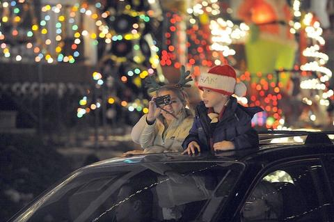 Wearing festive headgear, Addie Pfeiffer and nephew, Ethan Pullet, Timonium, take in the holiday light display from the sunroof as they ride along 34th Street in Hampden.