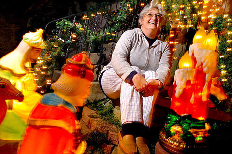 Hope Johnson sits proudly amid her 34th street home Christmas decorations including her newly purchased Christmans Candle (far right).