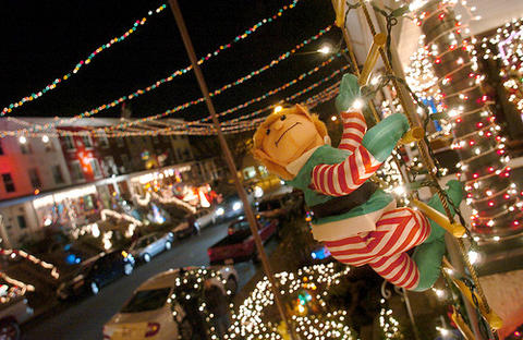 A stuffed Elf hangs on a rope ladder on the porch of a rowhouse in the 700 block of 34th Street in Hampden.