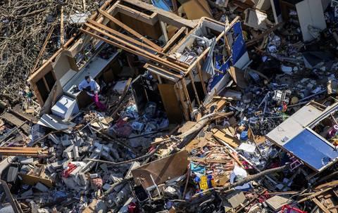 A person searches through the debris in Washington, Ill.