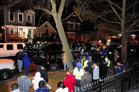 People gather across the street from a house that caught fire in the 2300 block of West 50th Place. One Chicago firefighter died from injuries sustained while fighting the blaze.