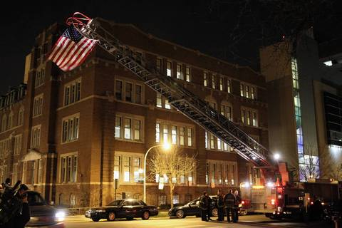 A flag hangs off a hook and ladder truck belonging to Truck Co. 16 outside the ER at University of Chicago Medical Center after a firefighter died from injuries sustained while fighting a house fire on Chicago's South Side.