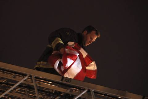 A Chicago firefighter removes a flag off the top of a ladder truck belonging to Truck Co. 16 outside the ER at University of Chicago Medical Center moments after the body of firefighter Captain Herbert Johnson was taken in procession to the Cook County Medical Examiner's Office.
