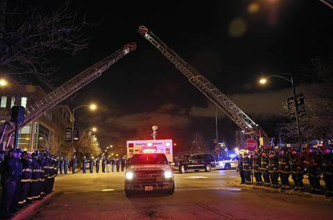 Firefighters salute as the ambulance carrying the body of Herbert Johnson heads to the Cook County Medical Examiner's Office.