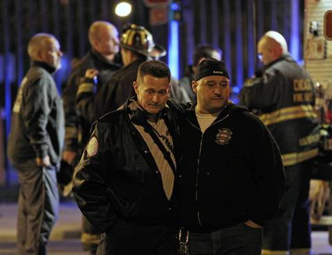 Two firefighters embrace while waiting for the ambulance carrying the body of Herbert Johnson to arrive at the Cook County Medical Examiner's Office.