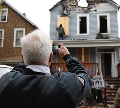A member of the Chicago Fire Department takes a photo of the aftermath of the fatal fire that killed his friend, Chicago Fire Department Capt. Herbert Johnson, at 2315 W. 50th Pl., in Chicago.