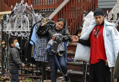 Rocio Castaneda carries away her possessions from her home in the 230 block of W. 50th Pl., in Chicago. Her family had rented an apartment at the address only three weeks ago. On the left is her son Christian Castaneda, 5. Chicago Fire Department Capt. Herbert Johnson died in the fire.