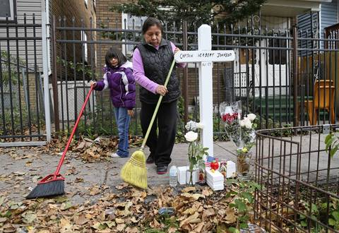 Edelmira Salvador, with her granddaughter, Bianca Leon, 9, sweeps the leaves around the memorial in front of her home which is next door to scene of a house fire that caused the death of Chicago Fire Department Capt. Herbert Johnson, in the 2300 block of W. 50th Pl., in Chicago.