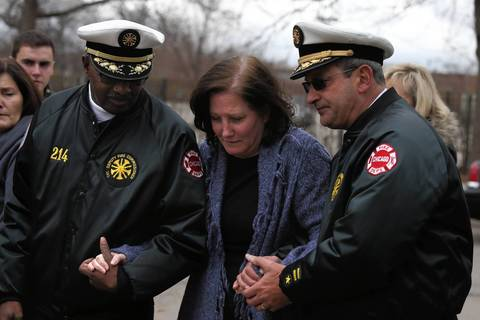 The wife of deceased Chicago firefighter Captain Herbert Johnson is helped to her car by two members of the Chicago Fire Department after a press conference outside of the Cook County Medical Examiner's Office.