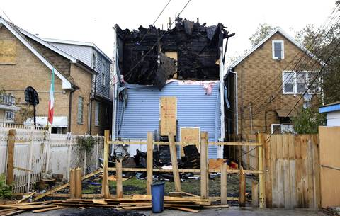The rear of the home shows extensive damage from the fire that killed Chicago firefighter Captain Herbert Johnson at the 2300 block of W. 50th Place in Chicago. An insurance company is suing the City of Chicago and the owners of a two-story building where a Chicago firefighter died last week, asking a judge to stop any future demolition of the site, claiming forensic evidence on the property must be preserved so its experts can complete their investigation.