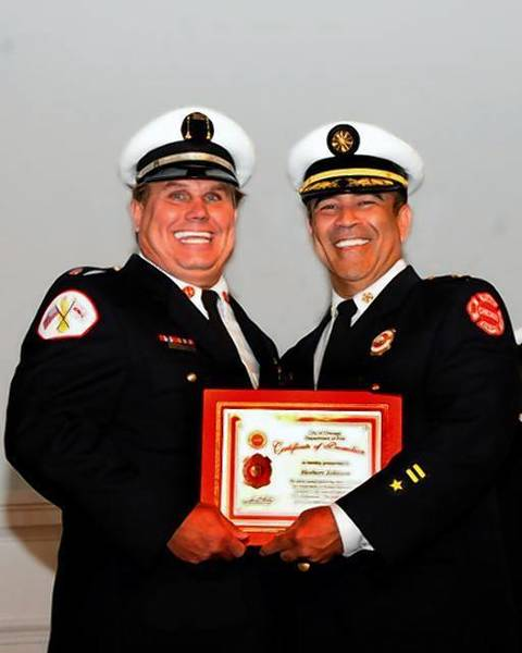 Chicago firefighter Herbert Johnson, left, poses with Chicago Fire Commissioner Jose Santiago, right, after Johnson was promoted to the rank of captain. Johnson died from injuries sustained while fighting a house fire on the South Side.