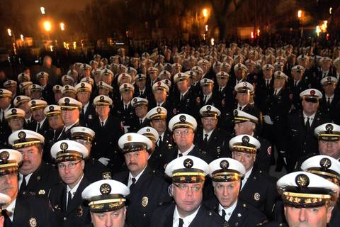 As night approaches firefighters from City of Chicago, the suburbs and other states gather outdoors at the wake for Chicago firefighter Captain Herbert Johnson at St. Rita of Cascia Chapel in Chicago. Johnson died fighting a fire last the previous week.