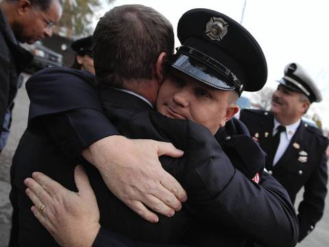 Firefighter Ted Johnson (right), the brother of Chicago firefighter Captain Herbert Johnson, hugs his friend Bill Bracken outside of St. Rita of Cascia Chapel in the 7700 block of S. Western Ave. in Chicago. Firefighters came for the wake of Herbert Johnson, who died from injuries sustained while fighting a house the previous week.