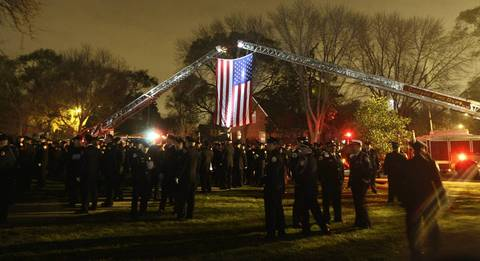 As night approaches firefighters from the City of Chicago, the Chicago suburbs, and states outside Illinois, gather outdoors at the wake for Chicago firefighter Captain Herbert Johnson at St. Rita of Cascia Chapel in Chicago. Johnson died in the line of duty the previous week.