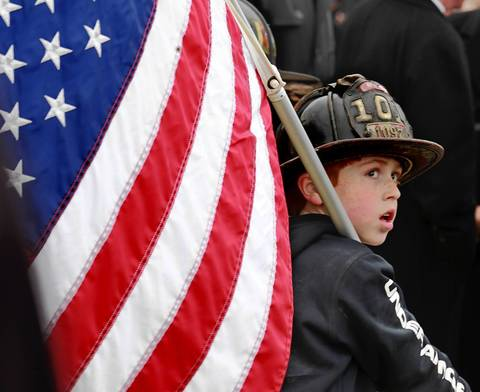 "Ten-year-old Packy Voves watches as the fire truck carrying Chicago firefighter Captain Herbert ""Herbie"" Johnson is brought to St. Rita of Cascia Shrine Chapel in Chicago."