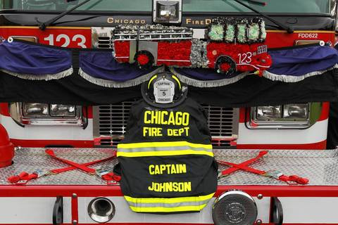 "Purple bunting and the firefighting gear of Chicago firefighter Capt. Herbert ""Herbie"" Johnson is displayed on the front of the fire truck that carried his casket to the funeral in Chicago."