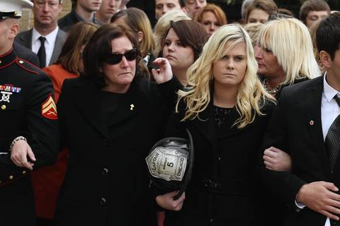 "Susan Johnson, the wife of Chicago firefighter Captain Herbert ""Herbie"" Johnson and his daughter, Laurie, holding his helmet, watch as his casket is carried into St. Rita of Cascia Shrine Chapel in Chicago."