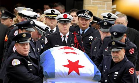 "The body of Chicago firefighter Captain Herbert ""Herbie"" Johnson is carried down the steps of St. Rita of Cascia Shrine Chapel, police officer (top right) is Herbert's brother John (CPD)"