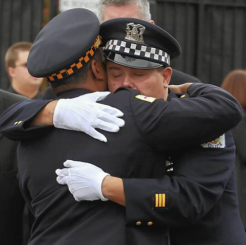"Chicago Police officer John Johnson, right, the brother of Chicago firefighter Captain Herbert ""Herbie"" Johnson, hugs another officer after the funeral service for Herbert at St. Rita of Cascia Shrine Chapel in Chicago"