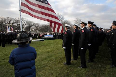 "Jack Voves, 11 holds a flag during funeral services for Capt. Herbert ""Herbie"" Johnson of the Chicago Fire Department at the Mt. Olivet Catholic Cemetery in Chicago. Jack's father, Jim Voves, served with Capt. Johnson on the same engine. Johnson, a captain and 32-year veteran, was killed while battling an extra-alarm fire in a Gage Park home."