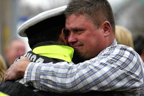 A member of the Johnson family, right, is embraced after a press conference outside of the Medical Examiner,s Office. Chicago firefighter Captain Herbert Johnson died fighting a fire the previous day.