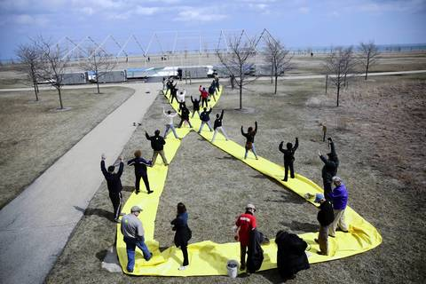 Friends of Meigs Field members hold down a yellow ribbon in front of the former airport terminal on Northerly Island in Chicago as private pilots flyover to mark the 10th anniversary of Mayor Richard Daley's destruction of the airfield. For more photos on Meigs Field: Click here to see our historical gallery.