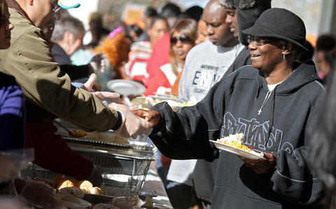 Barbara Hicks gets a Thanksgiving dinner at the annual Feeding 5000 community celebration at the Newport News Farmers market on Nov. 22. The annual event features local politicians and leaders serving food to people in need. No Mags, No Sales, No Internet, No TV