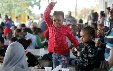 Elon Darden, 4, stands on her chair and dances as the Hertiage High band begins to play at the annual Feeding 5000 community celebration at the Newport News Farmers Market. No Mags, No Sales, No Internet, No TV