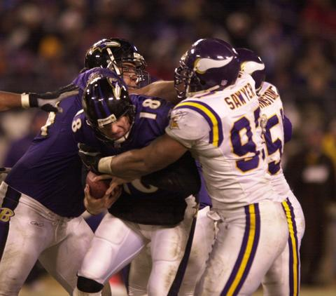 Ravens quarterback Elvis Grbac goes down in the grasp of Talance Sawyer in the third quarter.