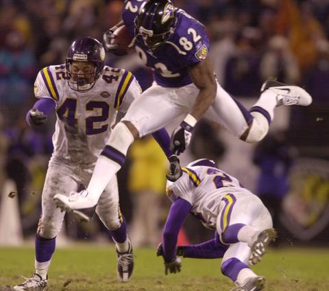 Shannon Sharpe goes over the top of the Vikings on a third-quarter reception.