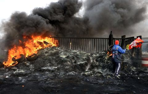 Employees of the US Goodyear company burn tires in front of the tyremaker site in Amiens, northern France, on December 5, 2013 after the announcement of the shutdown of the factory.