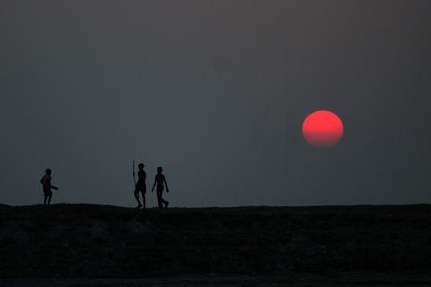 Indian youths look on across mudflats near the River Ganges as they wait to catch severed kites in Allahabad on December 5, 2013.