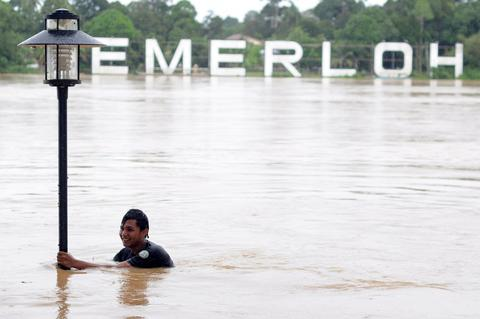 A youth holds on to a lamp post while playing in floodwaters in Temerloh, some 130 kms from Kuala Lumpur in Malaysia's central Pahang state, on December 5, 2013. Severe flooding in Malaysia has left a second person dead and two missing, while the number of evacuees has risen to some 56,000, a report and officials said on December 5.
