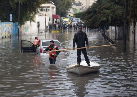 Palestinian civil defence try to remove a car submerged in a flooded street following heavy rainfall in Gaza City on December 5, 2013.