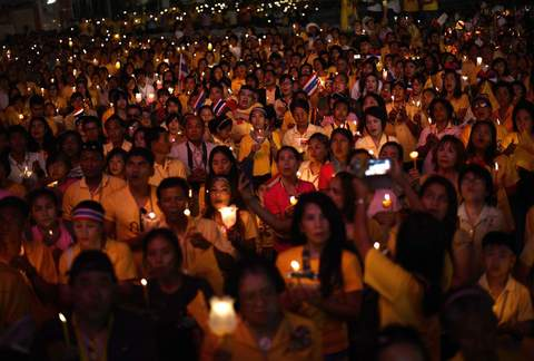 Anti-government protesters hold candles as they take part in birthday celebrations for Thailand's revered King Bhumibol Adulyadej, at the occupied government complex in Bangkok December 5, 2013.