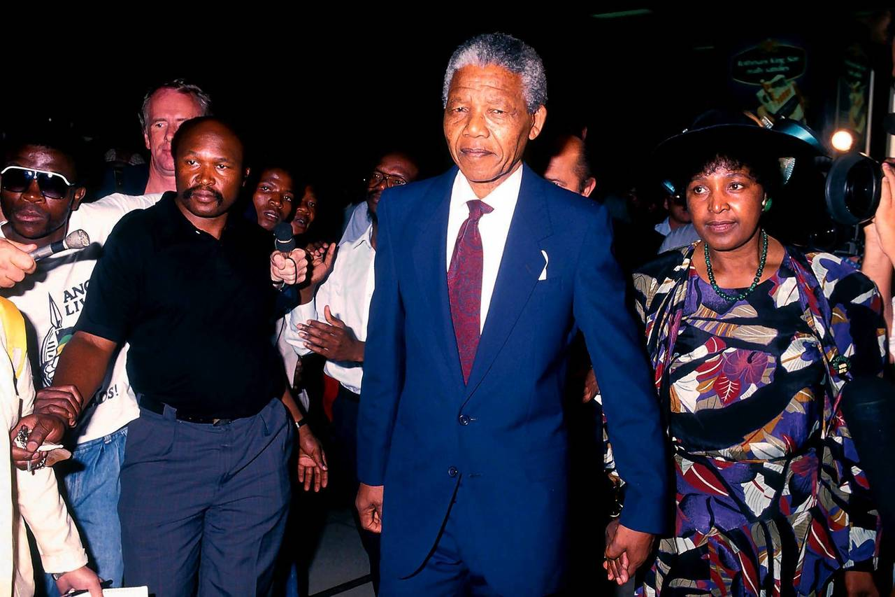 Former South African President Nelson Mandela and his wife Winnie Mandela pass through Johannesburg International airport, South Africa, before their departure for a trip to Zambia.