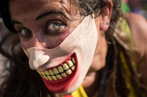 "A performers wears a mask during the ""Anjos do Picadeiro"" annual week-long event in Rio de Janeiro, Brazil, on December 5, 2013. About 100 clowns and street performers turn a street into a theater until December 7."
