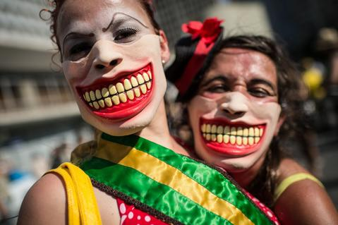 "Performers wear masks during the ""Anjos do Picadeiro"" annual week-long event in Rio de Janeiro, Brazil, on December 5, 2013. About 100 clowns and street performers turn a street into a theater until December 7."